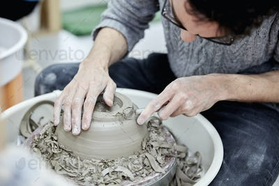 A man seated at a potter's wheel working and shaping a clay pot by removing excess clay.