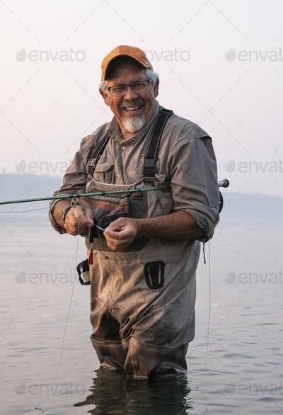 Caucasian senior male tying a fly on his fly fishing line while fishing for salmon and searun