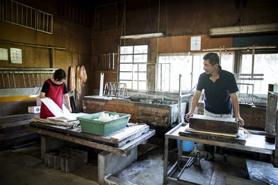 Two people, man and woman making traditional Washi paper. Trays of pulp and wooden frames and drying