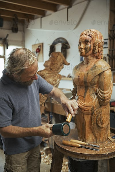 A wood carver standing in his workshop, using hand tools, mallet and chisel to shape and create
