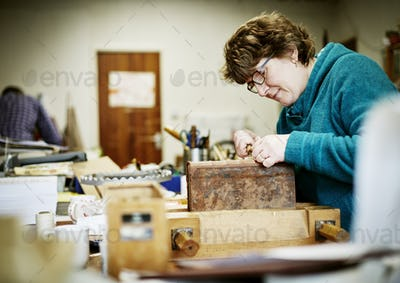 A woman working at a bench on the binding of a book in need of restoration.