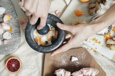 A woman's hand using a pestle and mortar on a kitchen counter.