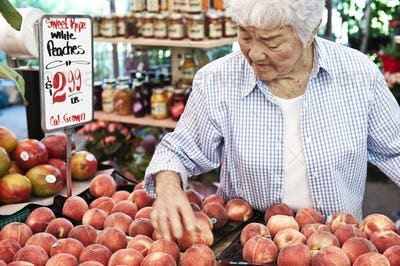Senior woman standing at stall with fresh white peaches at a fruit and vegetable market.