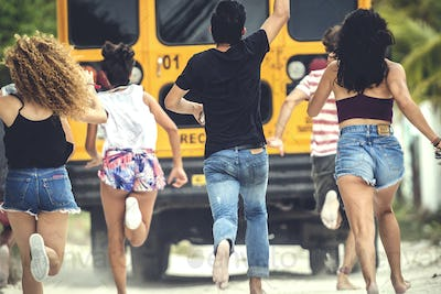 A group of young people chasing a moving school bus.