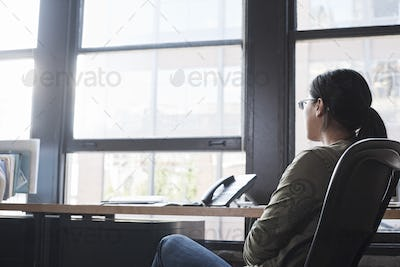 Asian woman working at her desk in a creative office.