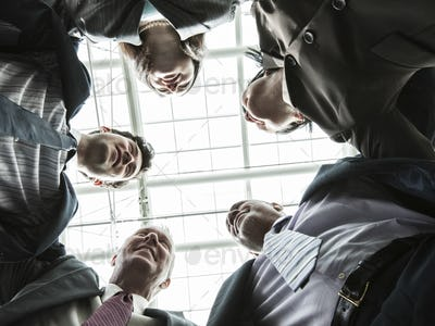 Mixed race group of business people standing in a team building circle.