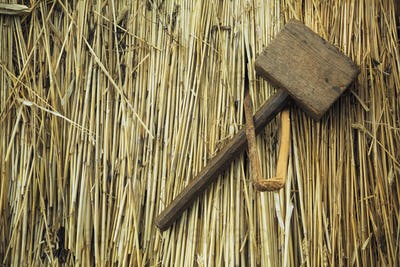 Close up of a wooden mallet and peg on a straw thatched roof.