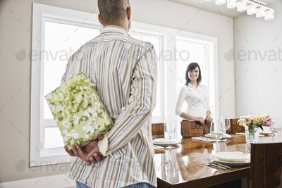 Hispanic man about to give his wife a wrapped present while standing in the dinning room of their