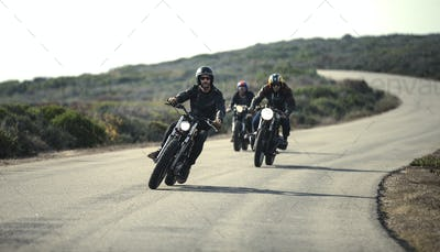 Three men wearing open face crash helmets and sunglasses riding cafe racer motorcycles along rural