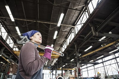 Black woman factory worker holding a large wrench in a sheet metal factory.