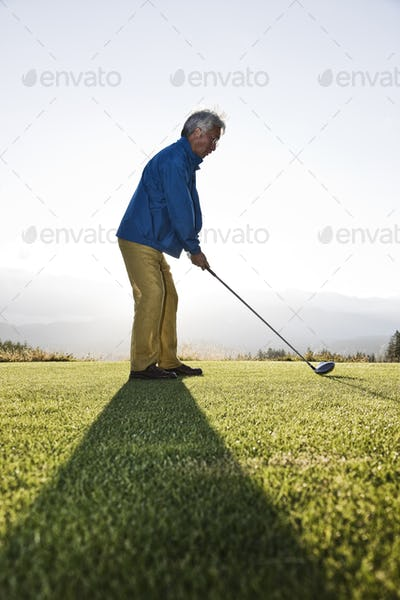 An asian senior man teeing up a golf ball and ready to swing.
