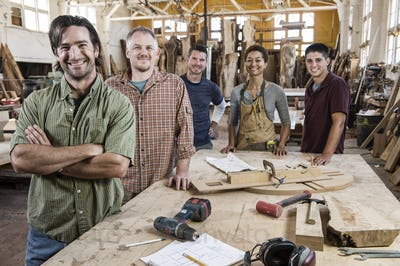 Team of multi-racial factory workers standing next to a work station in a large wood working