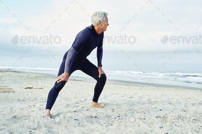 Senior man wearing wetsuit standing on a sandy beach.