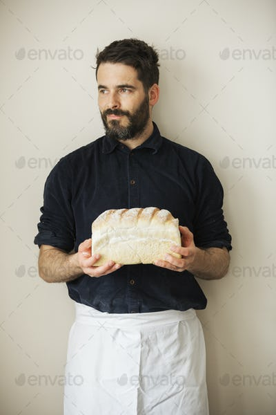 Baker holding a loaf of freshly baked white bread.