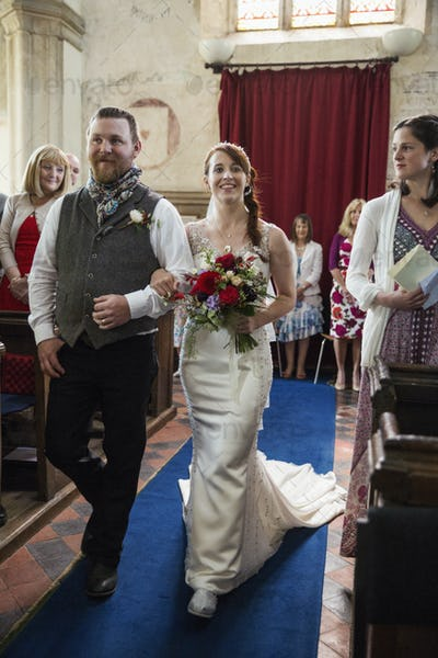 Smiling bride and groom walking down the isle in a church.