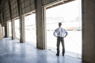 Caucasian man in shirt and tie standing in loading dock door of new empty warehouse anticipating the