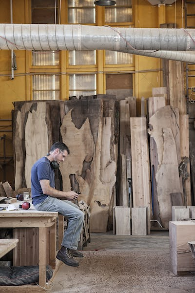 Caucasian man factory worker taking a break checking phone messages in a woodworking factory.