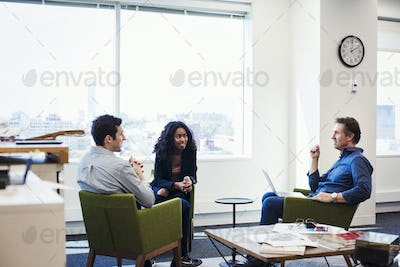 A woman and two men sitting in armchairs in an office talking to each other.