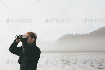 Middle aged man standing on a beach, looking through binoculars at Seabrook, Washington, USA.