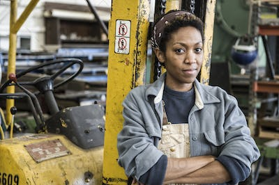 Black woman factory worker and a fork lift in a sheet metal factory.