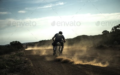 Rear view of man riding cafe racer motorcycle on a dusty dirt road.