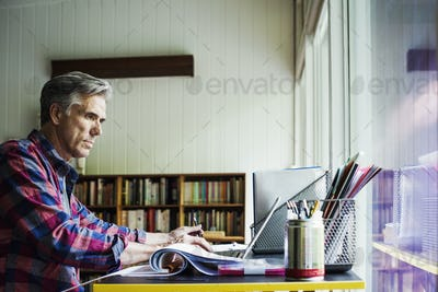 A man seated at a desk at home, working on a laptop computer.