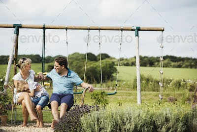 Man, woman and boy sitting side by side on a swing in a garden.