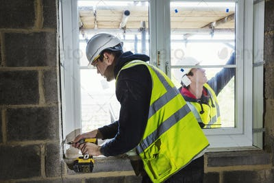 A workman on a construction site, builder in hard hat using an electric drill on a window sill.