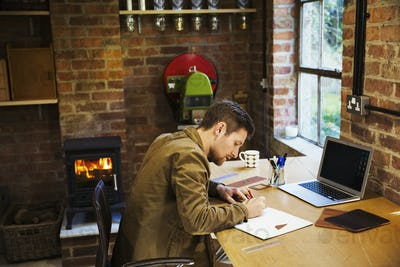 A designer seated in his leatherwork workshop, at a desk drawing on paper. A woodburning stove with