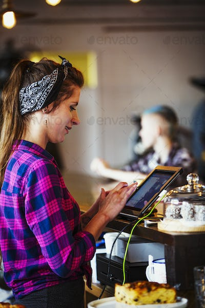 Specialist coffee shop. A woman working behind the counter using the touch screen on the till.