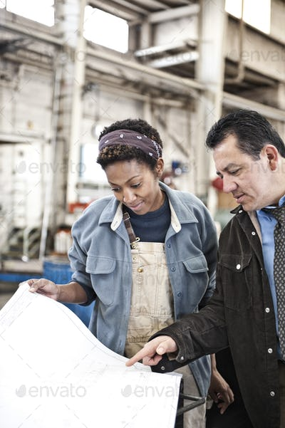 Hispanic man manager and black woman factory worker going over project plans in a sheet metal