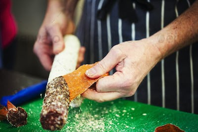 Close up of a butcher wearing a striped blue apron, taking the skin off a salami.