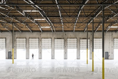 Owner silhouetted and standing in a loading dock door for a new empty warehouse.