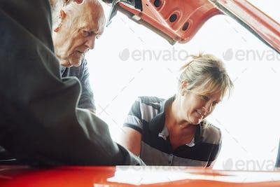 Mature woman and senior man repairing a car, looking under bonnet.