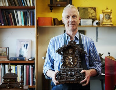 A clock maker and repairer holding an antique cuckoo clock.