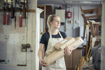 A young woman in a workshop, holding two packages wrapped in brown packaging paper, ready for