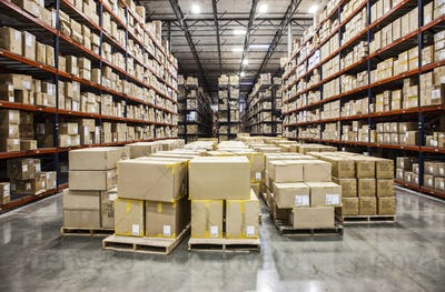 View down aisles of racks holding cardboard boxes of product on pallets  in a large distribution