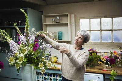 A florist working on a tall vase arrangement of flowers.