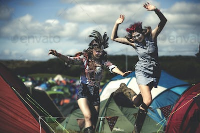 Two smiling young women at a summer music festival face painted, wearing feather headdress, jumping