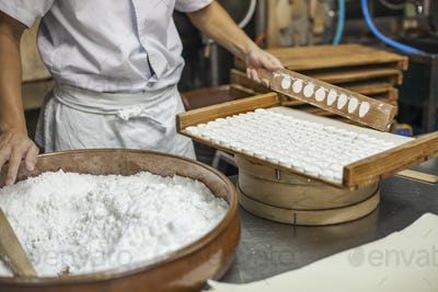 A small artisan producer of wagashi. A man mixing a large bowl of ingredients and pressing the mixed