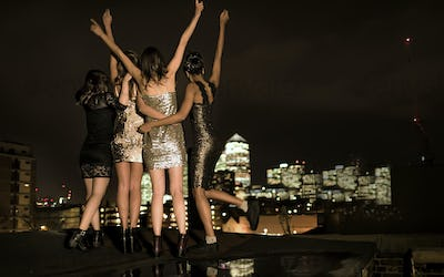 Group of young women standing on a rooftop celebrating.
