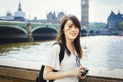 Young Japanese woman enjoying a day out in London, standing on the Queen's Walk by the River Thames.