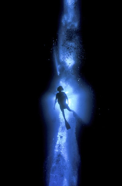 Diver silhouetted against the entrance to an underwater cave, Solomon Islands.