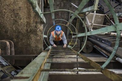 Factory worker climbing up a ladder in a sheet metal factory.