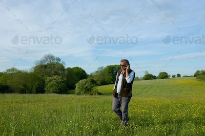 Man wearing sunglasses walking across meadow, holding mobile phone to his ear.