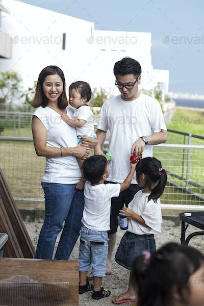 Portrait of smiling Japanese family with three young children standing in a back garden.