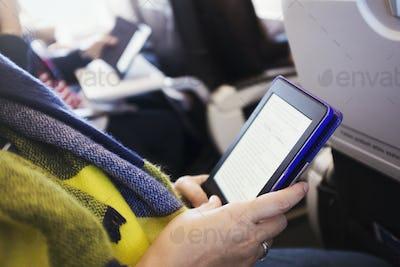 A passenger on an aircraft using a digital tablet.