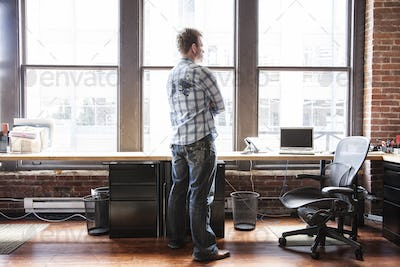Caucasian man standing near a bank of windows at his creative office workstation.