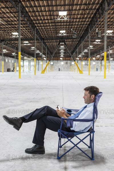 Caucasian man sitting in the middle of a new empty warehouse and using cell phone.
