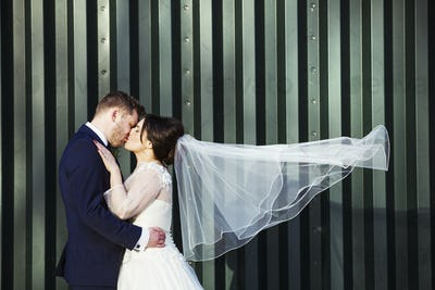 A bride and bridegroom on their wedding day, kissing each other.